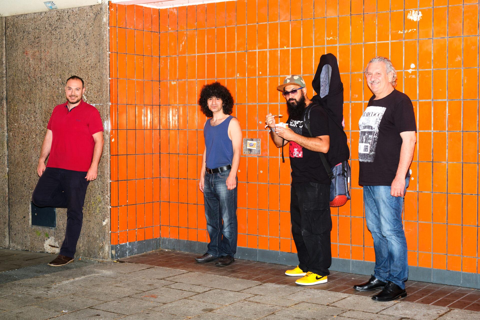 Vier Männer vor einer orange gefliesten Wand