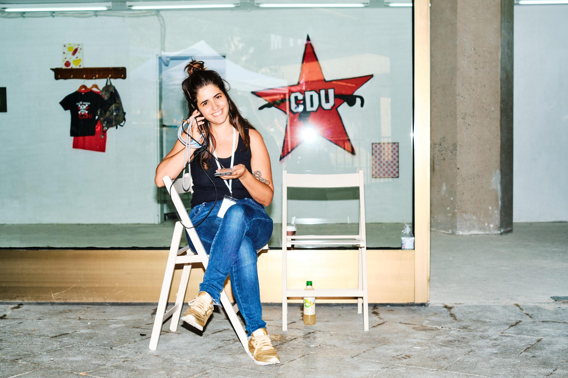 Frau sitzt auf einem Stuhl vor einer Galerie