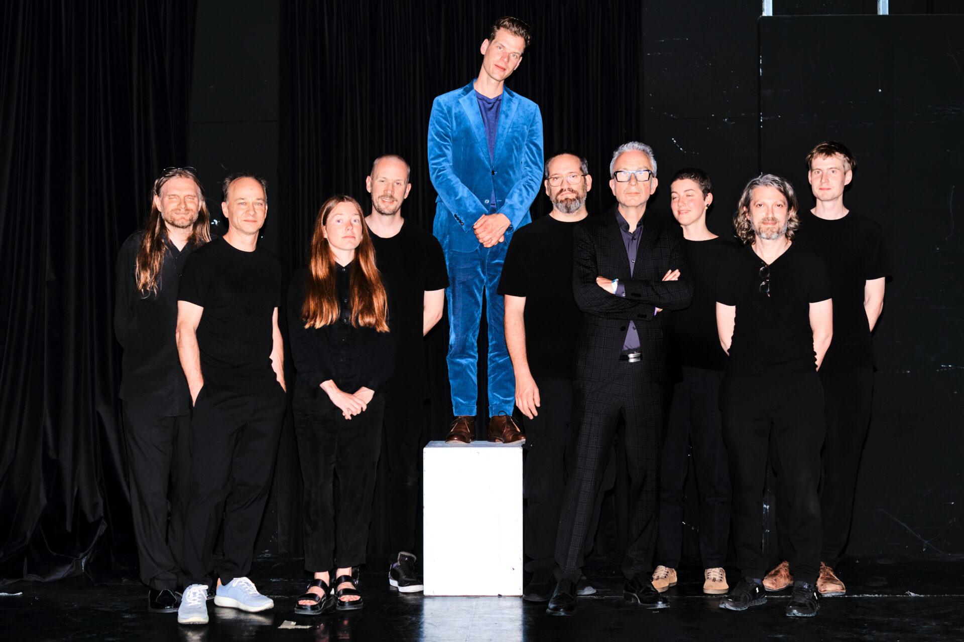 Mann im blauen Anzug steht auf einem weißen Sockel